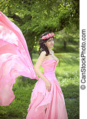 Beauty Romantic Girl Outdoors. Beautiful Teenage Model girl Dressed in blowing pink Dress on the Field at green park