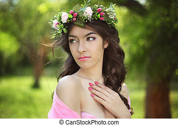 Beauty Romantic Girl Outdoors. Beautiful Teenage Model girl with flower chaplet at green park