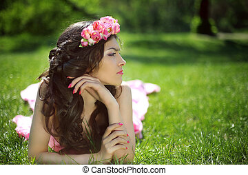 Beauty Romantic Girl Outdoors. Beautiful Teenage Model girl with flower chaplet lying on the green grass at park