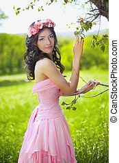 Beauty Romantic Girl Outdoors. Beautiful Teenage Model girl with flower chaplet posing in green field at park