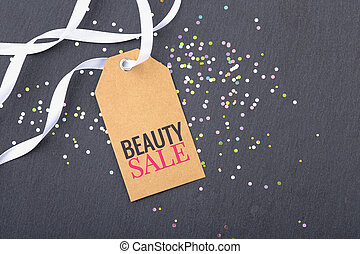 Beauty sale tag with white ribbon and glitter