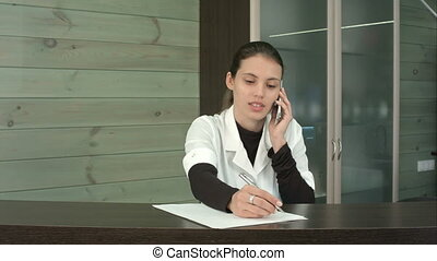 Beauty salon receptionist answering clients questions over...