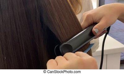 Beauty salon. Stylist cutting hairs of lady.
