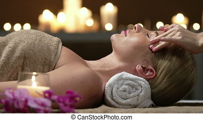Unrecognizable masseuse performing facial massage for blonde young lady resting head on towel roll