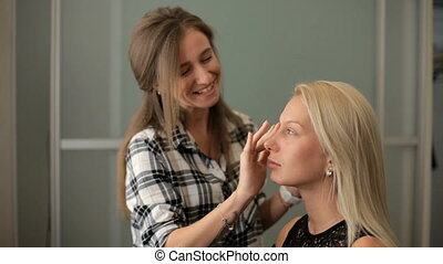 Beauty saloon A woman applies a blonde foundation to her...