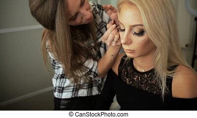 Beauty saloon Makeup artist draws arrows eyeliner blonde Eye...