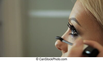 Beauty saloon Makeup artist induces eyelashes with a...