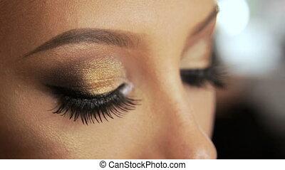 Beauty saloon Makeup artist induces eyelashes with a brush-mascara blonde Eye pencil