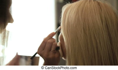 Beauty saloon Makeup artist paints eyebrows with a brush Blonde woman
