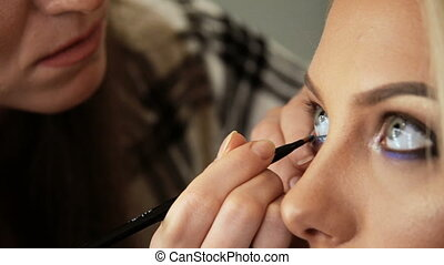 Beauty saloon Makeup artist paints the shadows on the eyes...