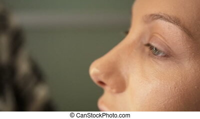 Beauty saloon Makeup artist puts sponge concealer blonde on...