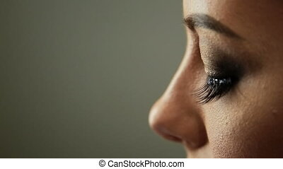 Beauty saloon Makeup artist sticks eyelashes to blonde eyes