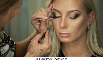 Beauty saloon Makeup artist sticks eyelashes to blonde eyes...