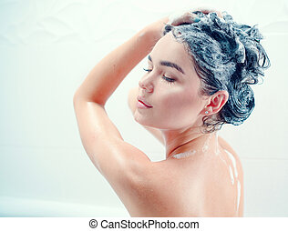 Beauty sexy model girl taking shower and washing her long black hair with a shampoo