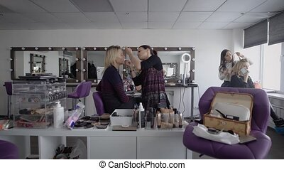Beauty shop. The master in a make-up trains three girlfriends to final at university. The girl applies with a shadow brush on top. The makeup artist professionally does a make-up.