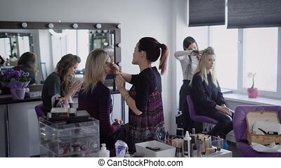 Beauty shop. Three models in beauty shop. Girls prepare for fashionable display. The makeup artist does a make-up to the fair-haired woman. The hairdresser does curls by means of the curling iron for hair.