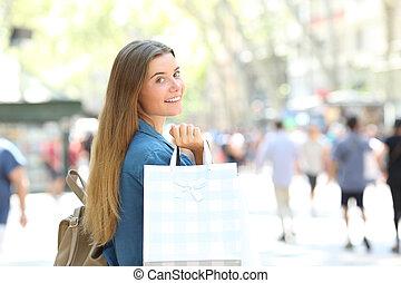 Beauty shopper showing shopping bags in the street