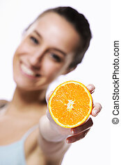 Beauty shot of a young woman with orange half on white background, focus on orange