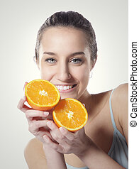 Beauty shot of a young woman with orange half on white background