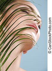 Beauty shot of beautiful woman looking trough leaf