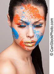 Beauty shot of posing model face with orange and blue dry colours. gold glitters on lips. FaceArt