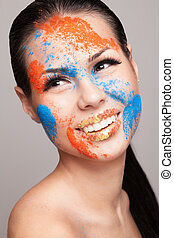 Beauty shot of smiling model face with orange and blue dry colours. gold glitters on lips. FaceArt