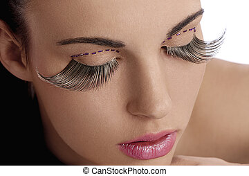 close shot of pretty and sensual brunette and creative make up with long eyelashes