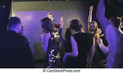 Beauty singer girl on stage and sings in karaoke bar -...