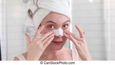 Girl Applying White Nose Patch On Facial Skin