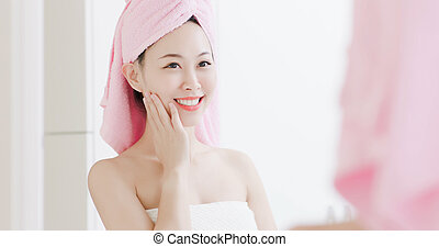 Beauty skin care woman look to mirror and touch her cheek after shower