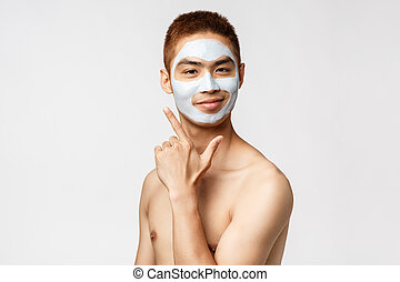Beauty, skincare and hygiene concept. Portrait of happy, pleased young asian man feeling beautiful, vibing at bathroom with facial cream, smiling like his face appearance, stand white background