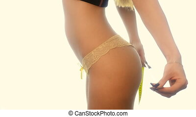 beauty slim woman in yellow panties measure her buttocks in studio