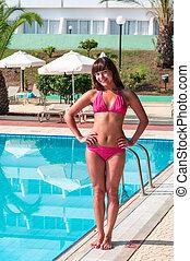 Beauty smiling woman in bikini standing near swimming pool
