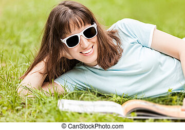 Beauty smiling woman reading book outdoor