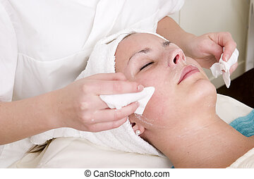 Lotion being wiped off during a facial at a beauty spa.