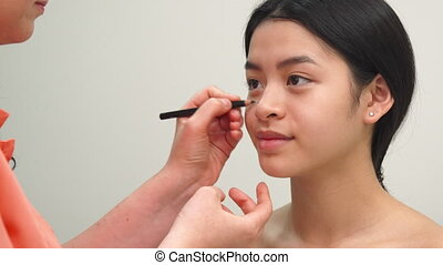 Beauty specialist uses cosmetic pencil