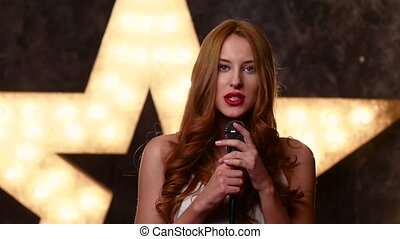 beauty star-girl singing with a microphone, slow motion, close up