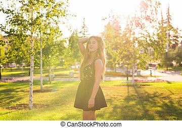 Beauty Sunshine Girl Portrait. Pretty happy woman enjoying summer outdoors.