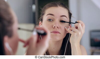 Beauty Teenage Girl applying Make up and admiring herself in the mirror. Attractive women Looking in the Mirror at home and listening music. Teen Fashion