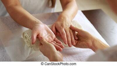 Beauty therapist massaging customers hands at the nail salon