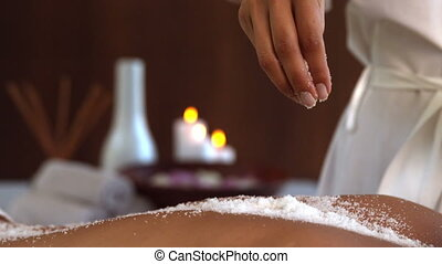 Beauty therapist pouring salt scrub on back in slow motion