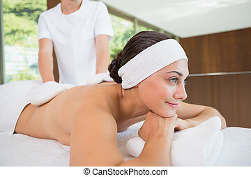Beauty therapist rubbing smiling womans back with heated mitts