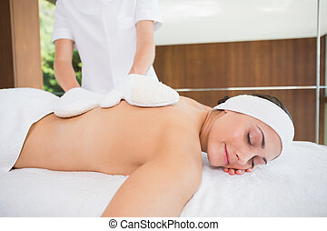 Beauty therapist rubbing womans back with heated mitts