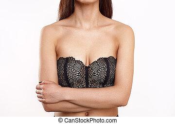 Beauty topless slim woman posing in black bra