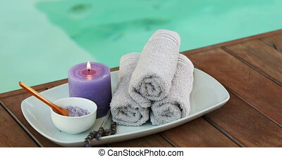 Beauty treatment in bowl presented on plate with candle at the spa