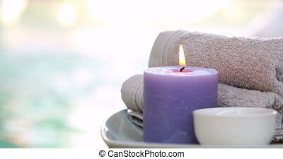 Beauty treatment in bowl presented on plate with candle at...