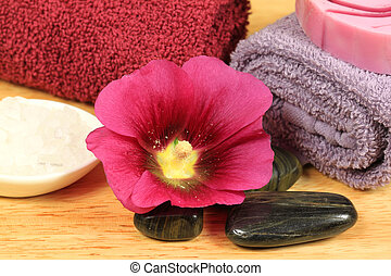 Beauty and wellness treatment in spa. Holyhock flower, massage stones and other care tools