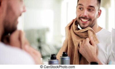 man wiping his face with towel at bathroom