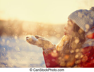 Beauty Winter Girl Blowing Snow in frosty winter Park. Outdoors