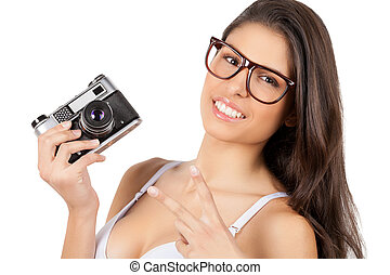 Beauty with camera. Attractive young woman in lingerie holding camera and gesturing